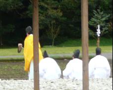 写真3 鍬打ちで作長が使用する風呂鍬。遠景は聖域であることを示す水田の四隅に立てられた飾り榊(2015年4月6日)