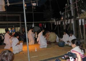 写真7 銀鏡神楽の花の舞。楽士の頭上の棚に6個のイノシシの頭部(2015年12月14日)