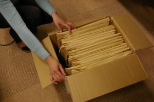 図1. 送付した質問票:大きな封筒の中に、学生、母、祖母用の3つの封筒に入った質問票が入っています。なるべく折れないように1箱に30家族分、立てて詰めました。この写真は参加者が回答した後、戻ってきたところです。封筒は各参加者に渡ったため少しよれよれになっていますが、送ったときと同じ形で返却してくださいました。(写真提供/『栄養と料理』女子栄養大学出版部)