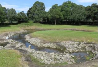写真3 城之越遺跡の復元された大溝。右に井泉、流れの合流付近に立石(2016年10月12日)